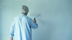 Young man painting wall during renovation home - stock footage