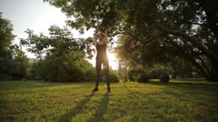 Young beautiful girl doing stretching on the grass in the Park Stock Footage