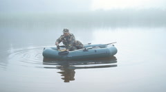 A fisherman casts anchor for inflatable boats. Early morning fog on the lake Stock Footage
