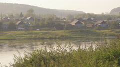 Russian wood village situated on banks of river in morning sun - stock footage