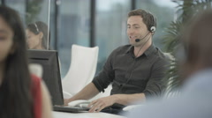 4K Friendly mixed ethnicity telesales team taking calls in busy call centre Stock Footage