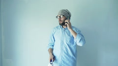 Young trendy man talking on cellphone during painting wall at his new home Stock Footage