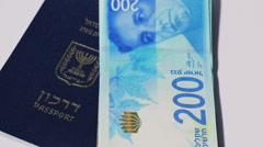 Rotating israeli money bills of 200 shekel and israeli passport  - top view s Stock Footage