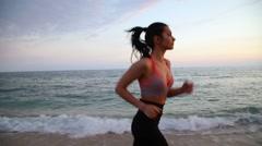 Sport leisure latina girl running on the beach of Mediterranean Sea at sunset Stock Footage
