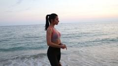 Sport leisure girl running on the beach of Mediterranean Sea at sunset Stock Footage