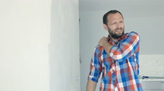 Young man having pain shoulder during painting wall, 4K Stock Footage