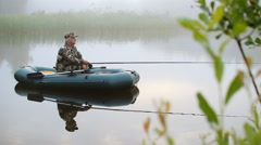 The fisherman on the boat fished. Small fish on a fishing rod - stock footage