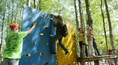 Children climbing on a pendant wall in the adventure park, Full HD footage Stock Footage