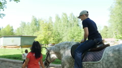 A happy kid riding a white horse in the adventure park, Full HD footage Stock Footage