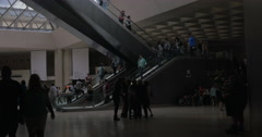 Louvre visitors on escalators in the Pyramid hall Stock Footage