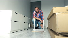 Portrait of young man assembling furniture in his new home Stock Footage