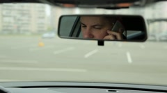 Man talking on the phone in the car mirror view - stock footage