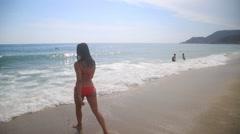 Latina girl walking into the sea Stock Footage
