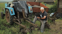 A man working on laptop near the tractor and move away. Agriculture surrounds Stock Footage