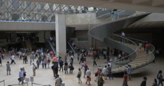 Crowded hall with spiral stairs in Louvre Pyramid Stock Footage