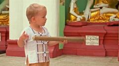Toddler boy strikes bell - stock footage
