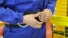 Man fastens a safety belt in warehouse Stock Footage