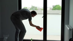 Young, tired man finish cleaning a window at his home Stock Footage