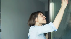 Young, angry woman cleaning a window at her home Stock Footage