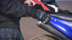 Biker in the street next to his bike, puts on gloves Stock Footage