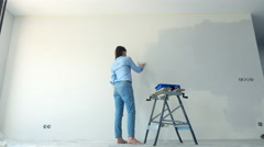 Young woman painting wall at her new home, 4K Stock Footage