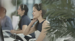 4K Friendly customer service operator taking calls in busy call centre Stock Footage