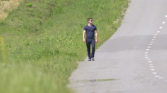 The man walk on the background of a hill. Real time capture. Wide angle - stock footage
