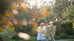 Young family painting on an easel in the garden Stock Footage