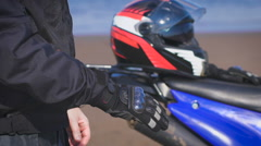 Biker in the street next to his bike, takes off his gloves Stock Footage