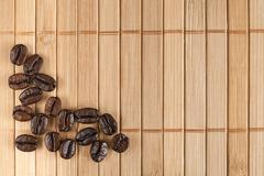 Scattered coffee grains on a bamboo napkin - stock photo