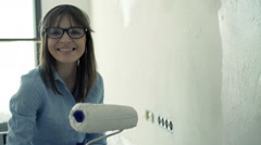Portrait of young woman painting wall at her new home Stock Footage
