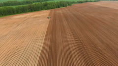 Farmer seeding, sowing crops at field.Aerial view - stock footage