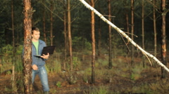 A man working on a laptop near a tree in the forest. Early morning Stock Footage