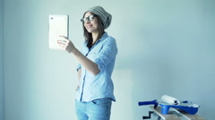 Young woman chatting on tablet during painting ker new home Stock Footage