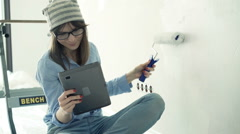 Young woman sitting with tablet during painting wall at her new home Stock Footage