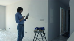 Young woman standing with tablet during painting wall at her new home Stock Footage