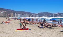 sunbathers at San Antonio Beach in Cullera, Spain - stock photo