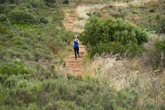 Sporty woman running downhill - stock photo