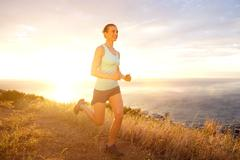 Active woman running outdoors during sunset - stock photo