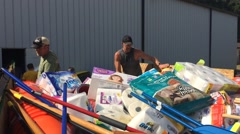 Men loading relief supplies into flatbed for flood victims (HD) Stock Footage