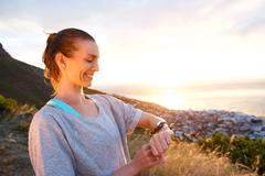 Woman smiling checking her watch for time by sunset Stock Photos