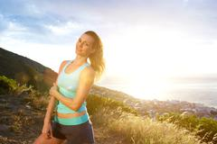 Beautiful fit woman standing outdoors - stock photo
