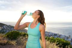 Active woman drinking from water bottle in front of the sea - stock photo
