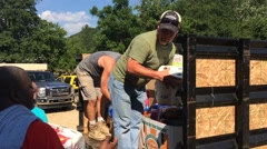 Men unloading supplies from flatbed for flood victims (HD) Stock Footage