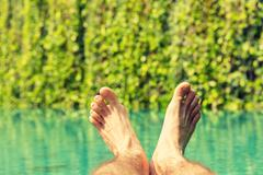 Close up of male feet over resort swimming pool Stock Photos