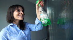 Young, pretty woman cleaning a window at her home, super slow motion Stock Footage