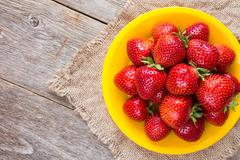 Plate with strawberries on piece of sackcloth - stock photo