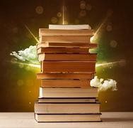 Magical books with ray of magical lights and colorful clouds - stock photo