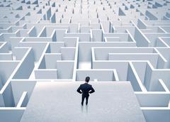 Businessman staring at infinite maze - stock photo