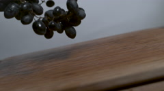 Bundle of purple grapes falling and rolling onto a cutting board in slow motion Stock Footage